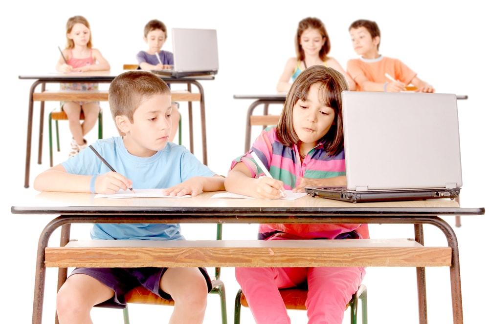 Schulkinder mit Notebook auf weißem Hindergrund